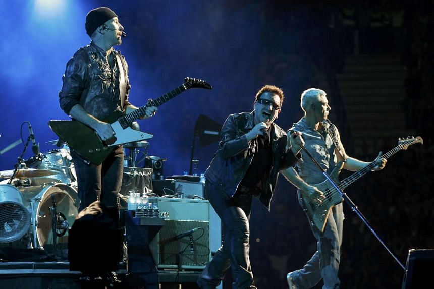 Lead singer Bono (centre) of Irish rock band U2 performs with The Edge (left) and Adam Clayton (right) during their 360 Degree Tour in 2010.