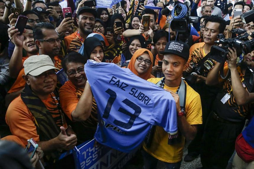 The Fifa Puskas Award winner Mohd Faiz Subri holds his jersey with his fans after arriving at the Kuala Lumpur International Airport on Jan 11, 2017.