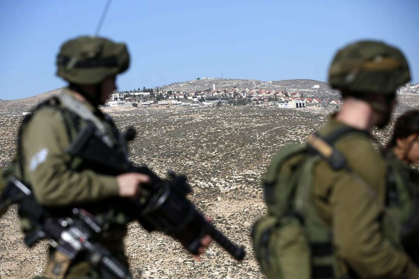 An Israeli settlement is seen on a hillside (background) as Israeli army soldiers stand guard while a bulldozer (unseen) closes a road in what is called 'Area C' near the West Bank village of Bani Naem, on Jan 11, 2017.