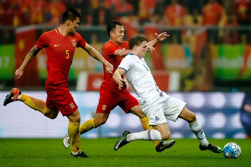 Bjorn Bergmann Sigurdarson (right) of Iceland fights for the ball with Fan Xiaodong and Yang Shanping of China during their 2017 Gree China Cup International Football Championship match at in Nanning, China on Jan 10, 2017.