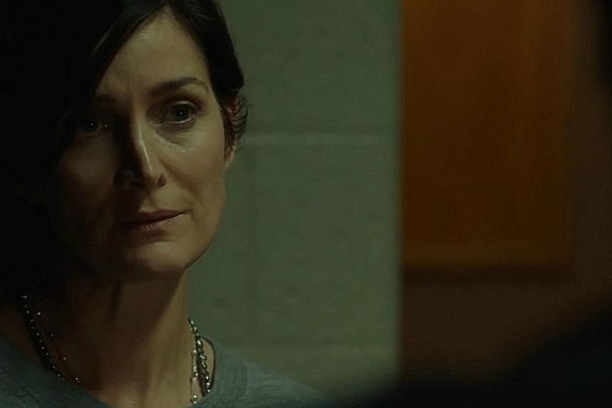 Carrie-Anne Moss (above) is a cop in The Bye Bye Man who refuses to believe that a bogeyman is killing college students Lucien Laviscount, Douglas Smith, and Cressida Bonas.