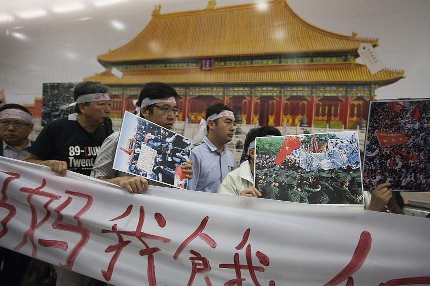 Pro-democracy protesters gathering in front of a banner advertising the Palace Museum project at the Central MTR station on Monday. Mrs Lam has come under fire for not seeking public feedback before signing the MOU on the development of the museum.