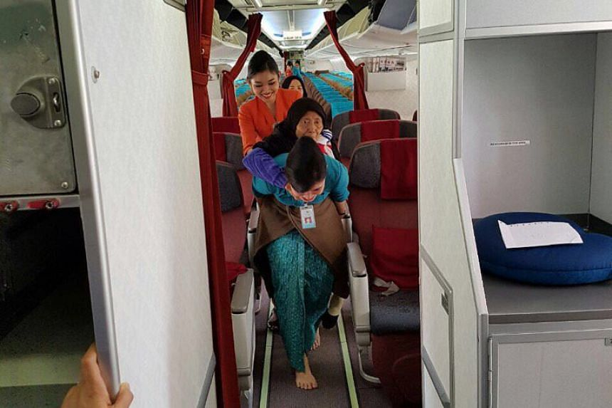 Two Garuda Indonesia flight attendants have been lauded for helping an elderly wheelchair user move from her seat to the exit door.