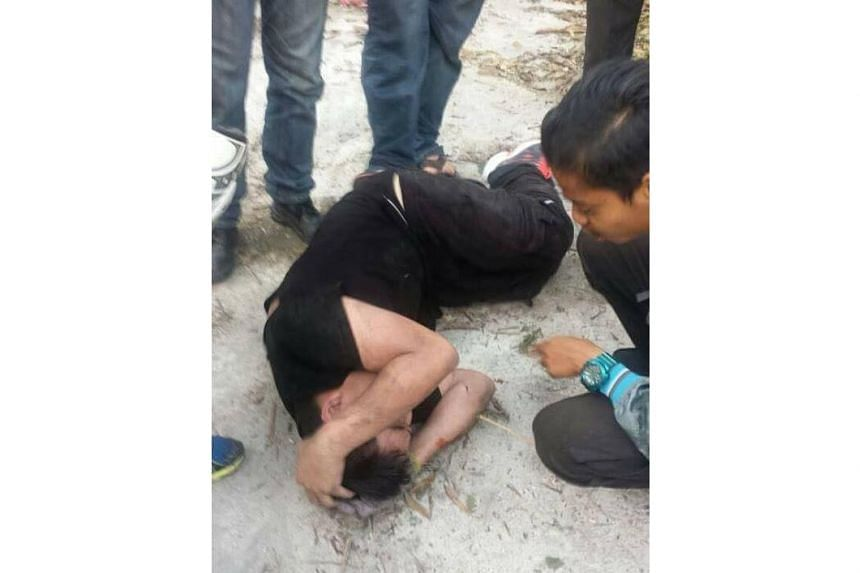 One of the suspected kidnappers lie on the ground after being beaten by an angry mob in Selangor on Jan 11, 2017.