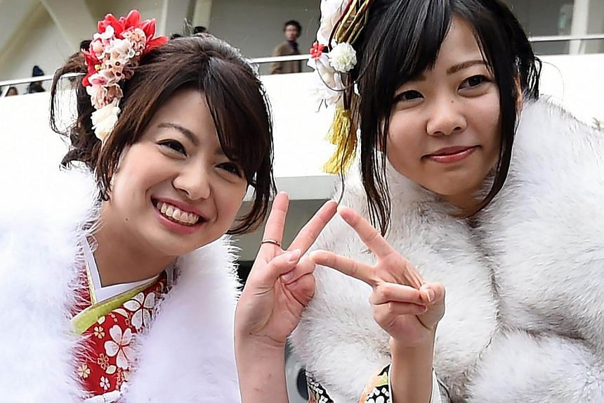 20-year-old Japanese women posing for photographers with peace signs before their Coming-of-Age ceremony at the Tokyo Disneyland in Urayasu, suburb of Tokyo.