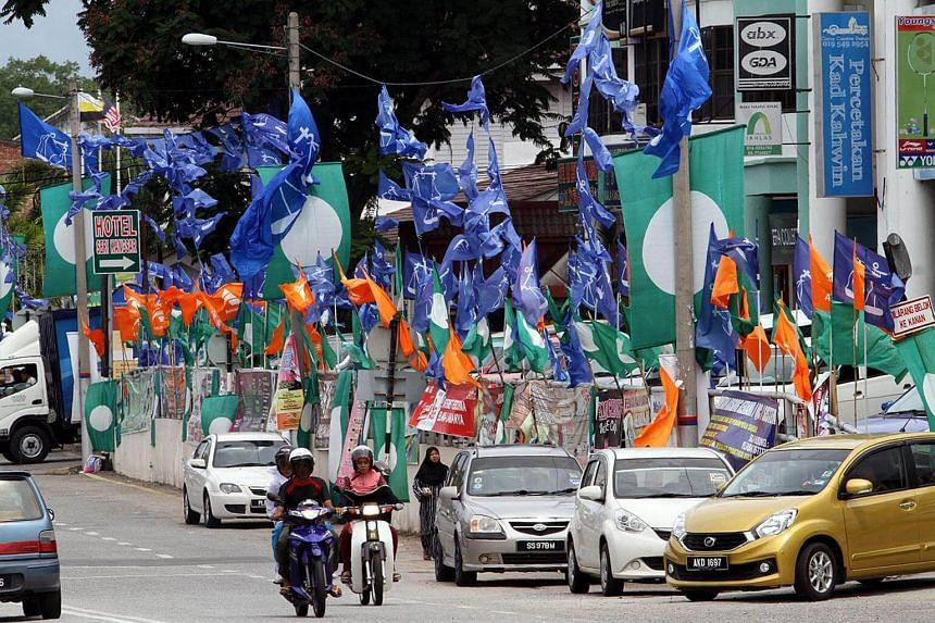 Flags and banners of opposition rivals Parti Islam SeMalaysia and Parti Amanah Negara, as well as those of the ruling Barisan Nasional coalition, lining a street in Kuala Kangsar, Perak, during campaigning for the by-election in June 2016.