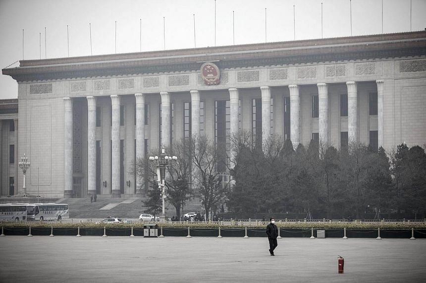 A man wearing a face mask walks past the the Great Hall of the People shrouded in haze in Beijing, China, on Jan 6, 2017.