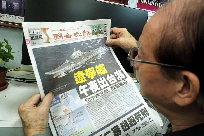 A man read reading afternoon daily United Evening News' report on China's aircraft carrier Liaoning that passed through the Taiwan Strait, in Taipei, Taiwan, on Jan 11, 2017.