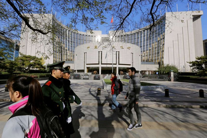 People walk past the headquarters of the People's Bank of China in Beijing.