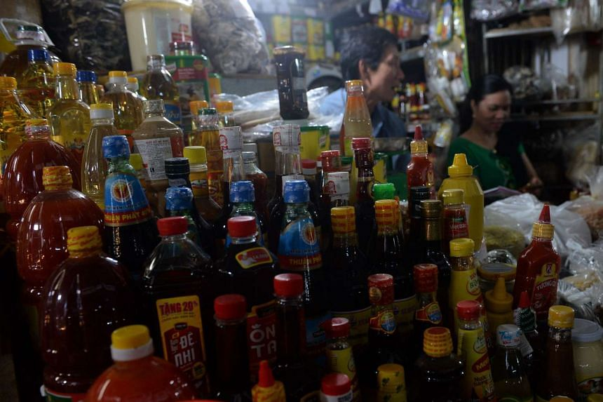 Vendors sits next to bottles of different sauce including fish sauce at a stand inside a local market in downtown Hanoi on Nov 21, 2016.