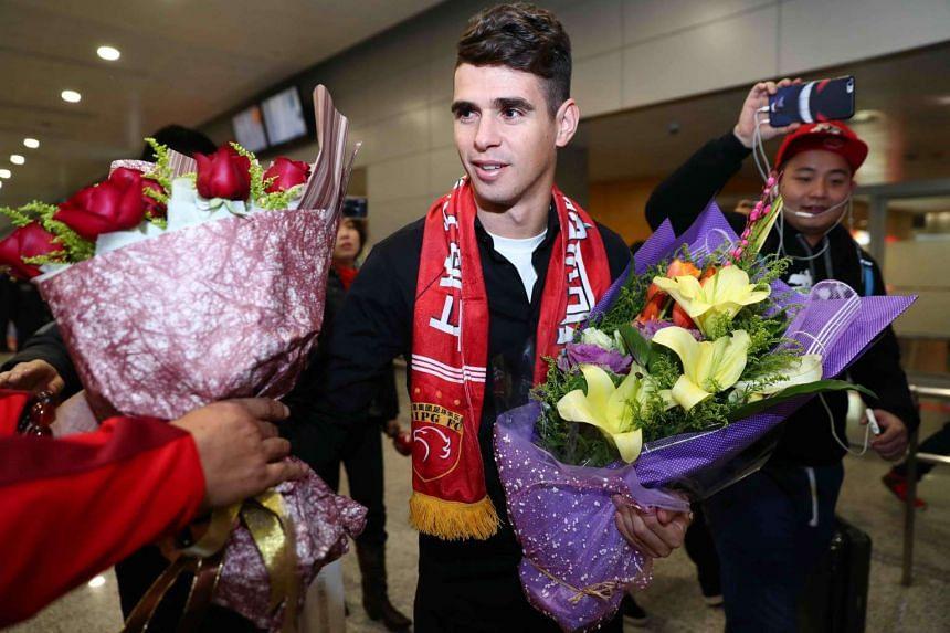 Brazilian football player Oscar (centre) receives flowers as he arrives at Shanghai airport on Jan 2, 2017.