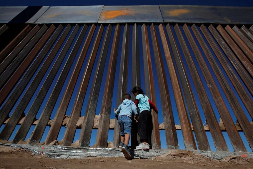 Children play at a newly built section of the U.S.-Mexico border wall at Sunland Park, US opposite the Mexican border city of Ciudad Juarez, Mexico on Nov 18, 2016.