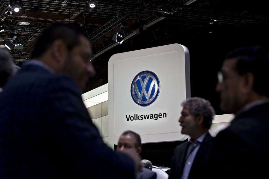 Attendees stand in front of a Volkswagen sign during the 2017 North American International Auto Show in Detroit, Michigan, Jan 10, 2017.
