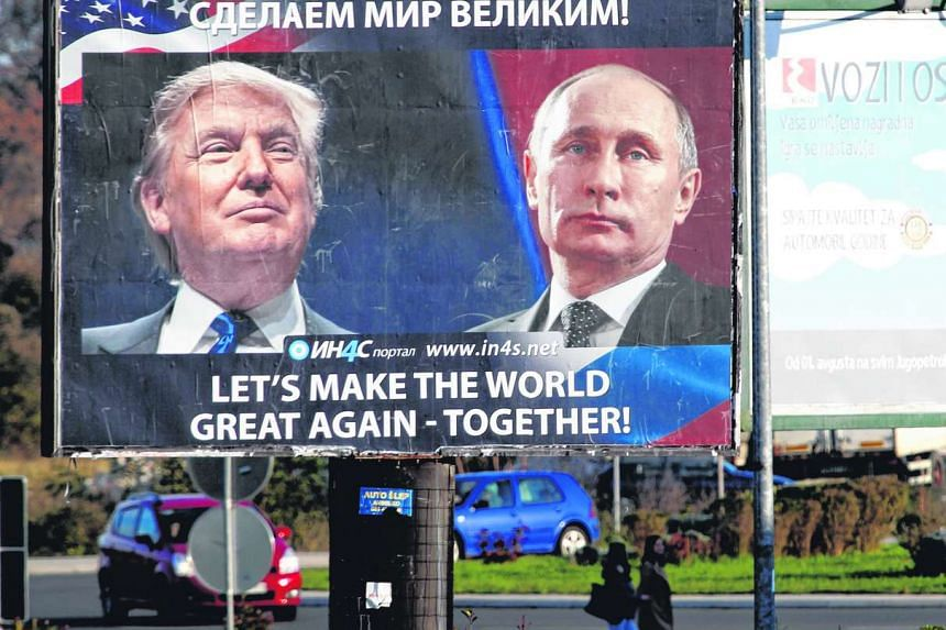 Pedestrians cross the street behind a billboard showing a pictures of US president-elect Donald Trump and Russian President Vladimir Putin in Danilovgrad, Montenegro, on Nov 16. 2016.