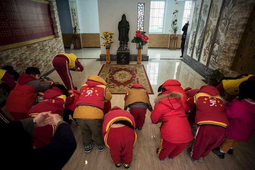 Children bowing before a statue of Confucius after a class at a Confucius kindergarten in Wuhan.