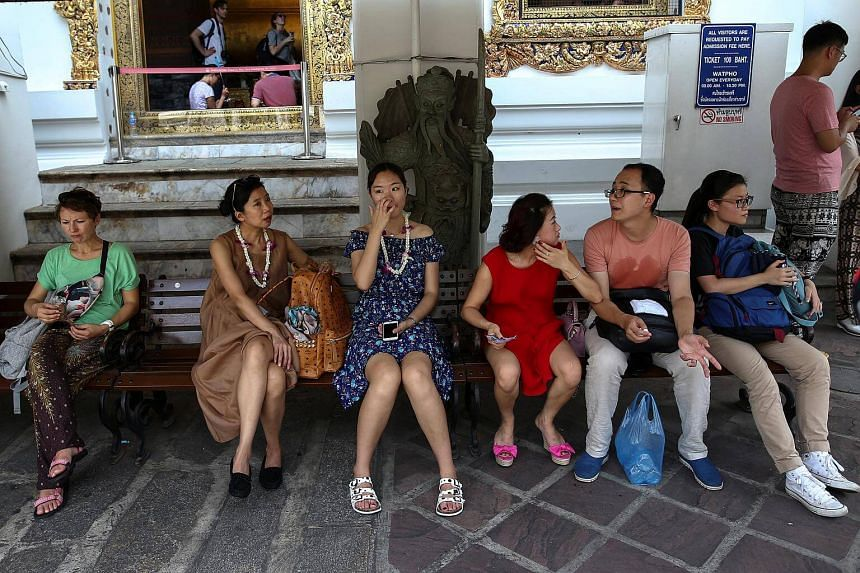 Chinese tourists take a break at Wat Pho in Bangkok, Thailand on Oct 3, 2016.