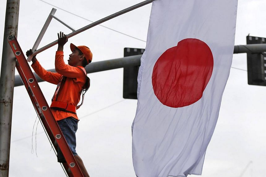 Filipino government workers hang a Japanese flag at a street in Manila, Philippines, on Jan 11, 2017.