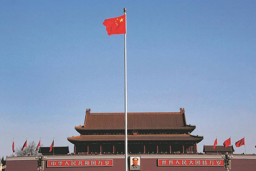 China's nation flag flies on Tiananmen Square in front of the portrait of the former chairman Mao Zedong at the Great Hall of the People in Beijing, on Mar 14, 2012.