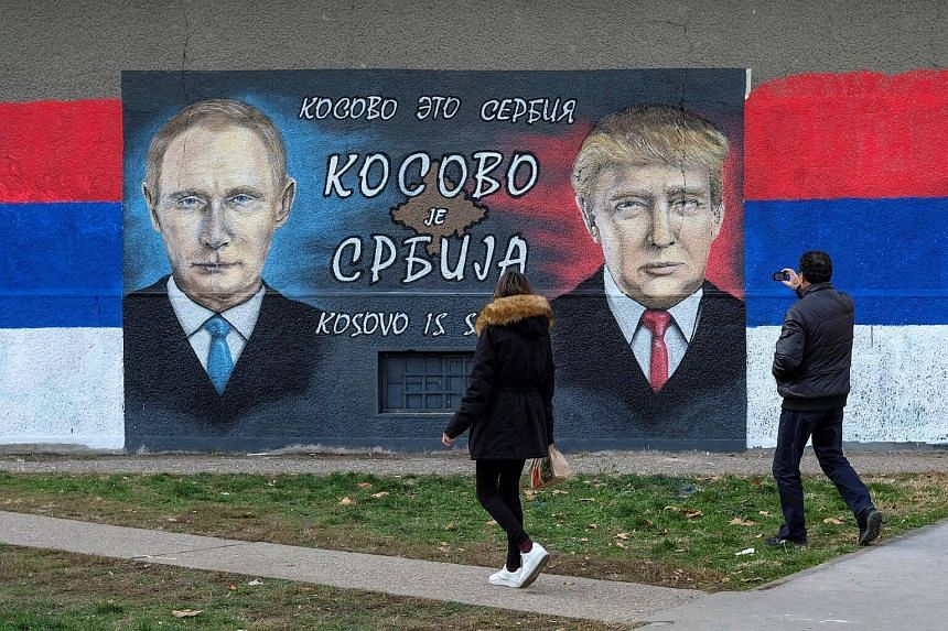 A man takes pictures of a mural of U.S. president-elect Donald Trump and Russian President Vladimir Putin in Belgrade, Serbia on Dec 4, 2016.