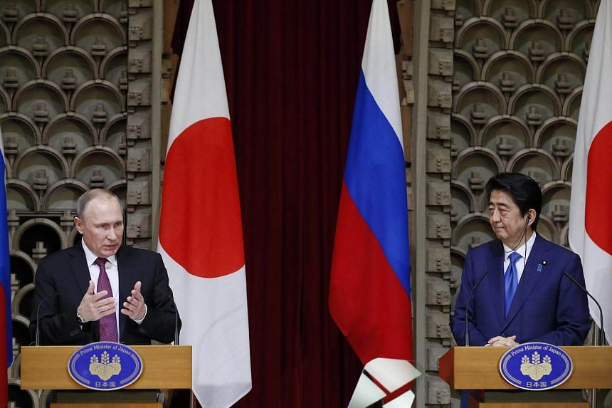 Russian President Vladimir Putin speaks as Japanese Prime Minister Shinzo Abe listens during a joint news conference in Tokyo, Japan, on Dec 16, 2016.