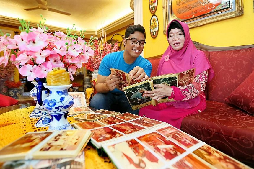 Mr Hafiz Rashid has been learning the language on his own to rediscover his Baweanese roots. He has attended classes and watches YouTube videos (below) of Baweanese songs. Madam Romnah Salleh and her son, Mr Khairul Basysyar Amran, going through phot