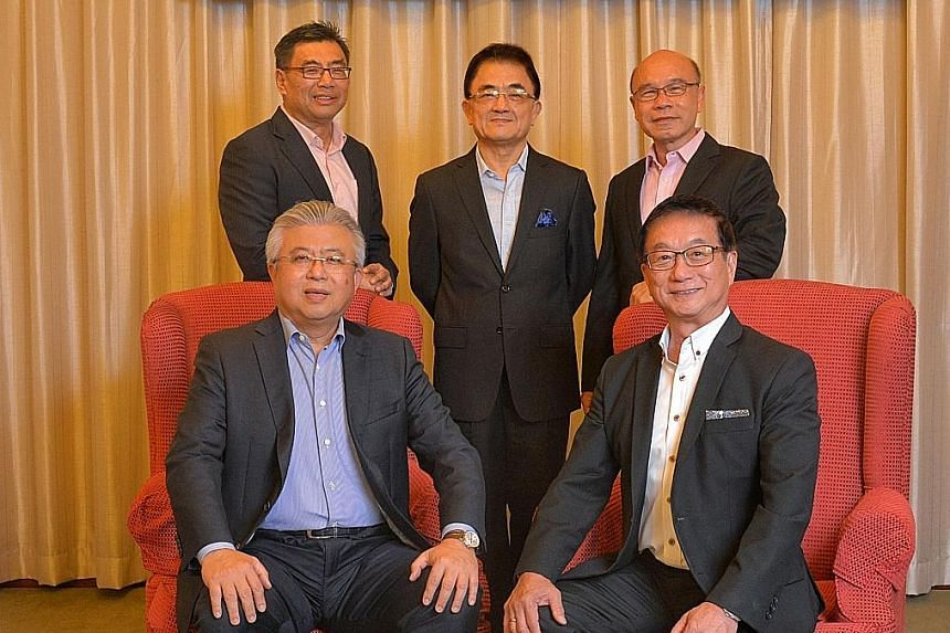 Mr Thomas Chua (seated left), president of the 58th Council, and Mr Roland Ng, the new president. Standing, from left: Vice-presidents Kuah Boon Wee, Wu Hsioh Kwang and Charles Ho Nai Chuen.