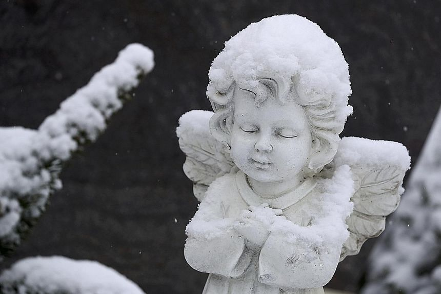 A statue blanketed in snow in the main cemetery of the German town of Hanau, near Frankfurt.