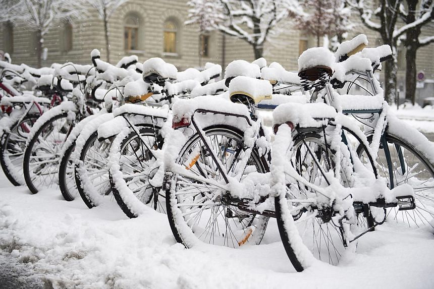 Bicycles sit unused along a street in Bern. The heavy January snowfall comes after a long absence of snow in Switzerland, where the fickle winter weather has left some ski resorts with closed slopes and a drop in tourist numbers.