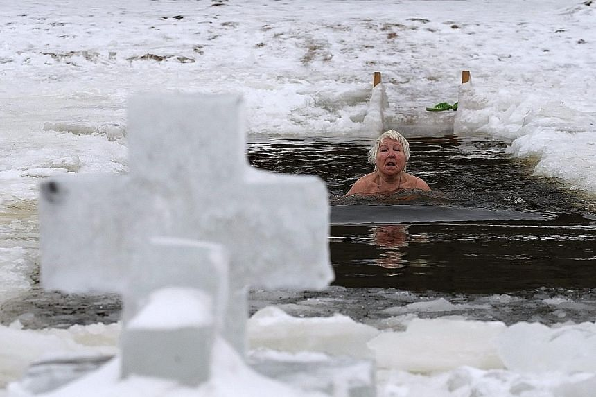 An elderly bather braving the ice in the Neva River in St Petersburg, where temperatures were around 0 deg C.
