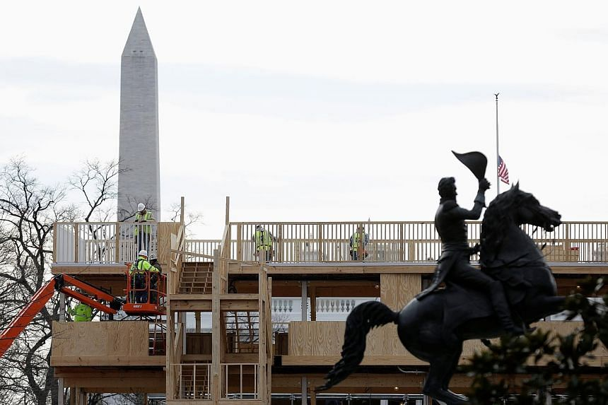 """Workers building a reviewing stand for the upcoming presidential inauguration near the White House yesterday. The Trump team has struggled to attract A-list entertainers to flesh out the Jan 20 event, but said the event would have """"poetic cadence"""" ra"""