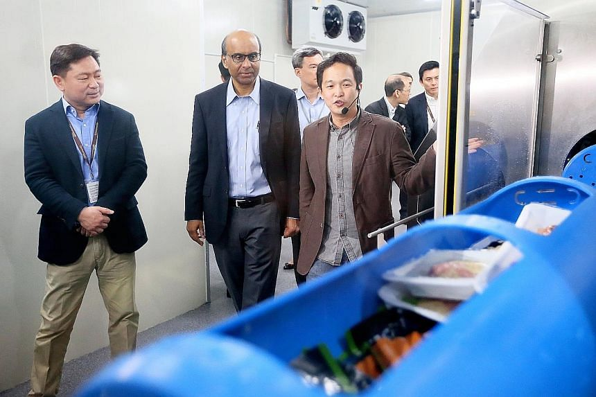 DPM Tharman, accompanied by Mr Kwan (left), being shown how a high-pressure processing line works. Mr Chan (right) said the machine could increase the shelf life of The Soup Spoon's soup sachets from two weeks to three months, which would allow the c