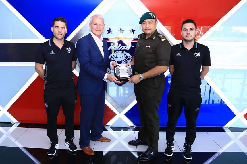 Peter Draper, Valencia's commercial and marketing director, and Captain Mohd Fahmy Yahya, JDT's honorary secretary, with a model of the Mestalla. They are flanked by the Spanish club's coaches, Gonzalo Sanz Zaballos (left) and Jose Requena, who