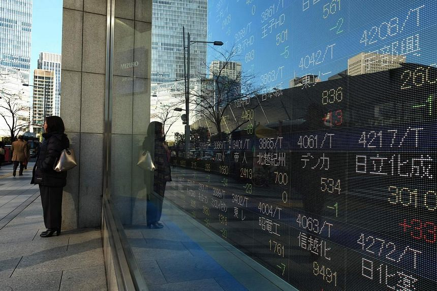 A pedestrian stands in front of an electric quotation board flashing numbers of the Nikkei key index morning session of the Tokyo Stock Exchange in Tokyo on Jan 12, 2017.