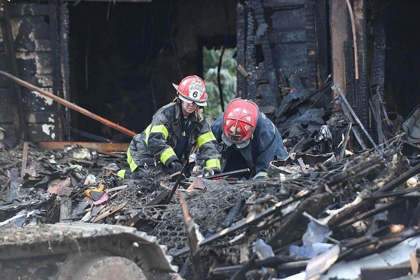 Firefighters sift through debris at the scene of an overnight house fire, where several children were presumed dead and others including the mother injured, in Baltimore, Maryland.