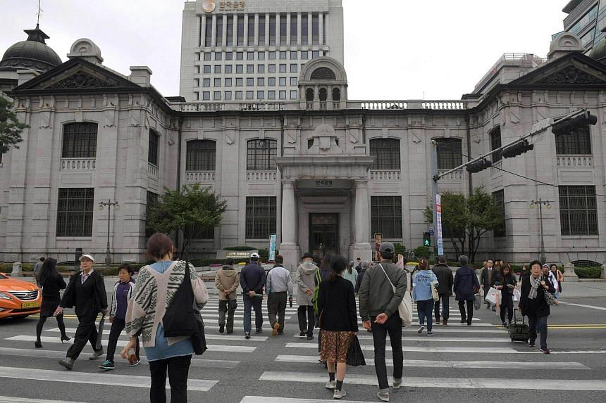 People walk across the road in front of the Bank of Korea in Seoul on Oct 25, 2016.