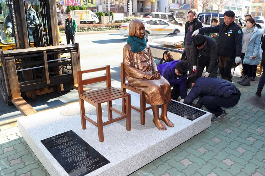 """This picture taken on Dec 30, 2016 shows workers setting up a statue of a teenage girl symbolising """"comfort women"""" outside the Japanese consulate in Busan."""