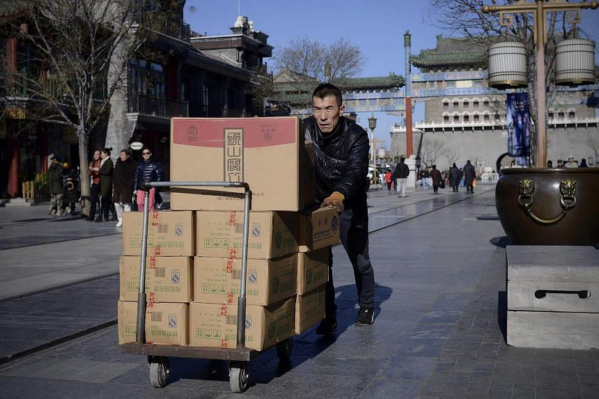 A man pushes a trolley with goods along a street in Beijing on Jan 10, 2017.
