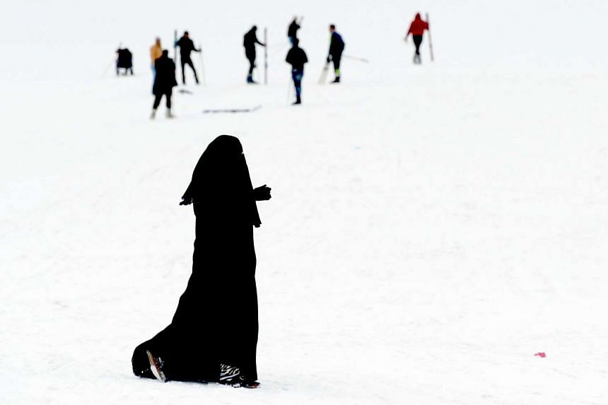 A woman wearing a niqab walks on the snow at the Oukaimeden ski resort, in the Atlas Mountains.