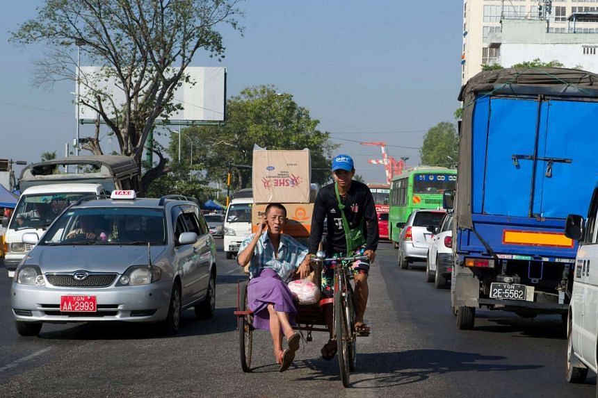 A man using a mobile phone transports his goods in a trishaw in central Yangon's busy Strand Road, on Dec 14, 2016.