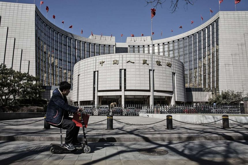 A man riding a scooter past the People's Bank of China headquarters in Beijing, China. Chinese banks extended a record 12.56 trillion yuan (S$2.61 trillion) of loans last year.