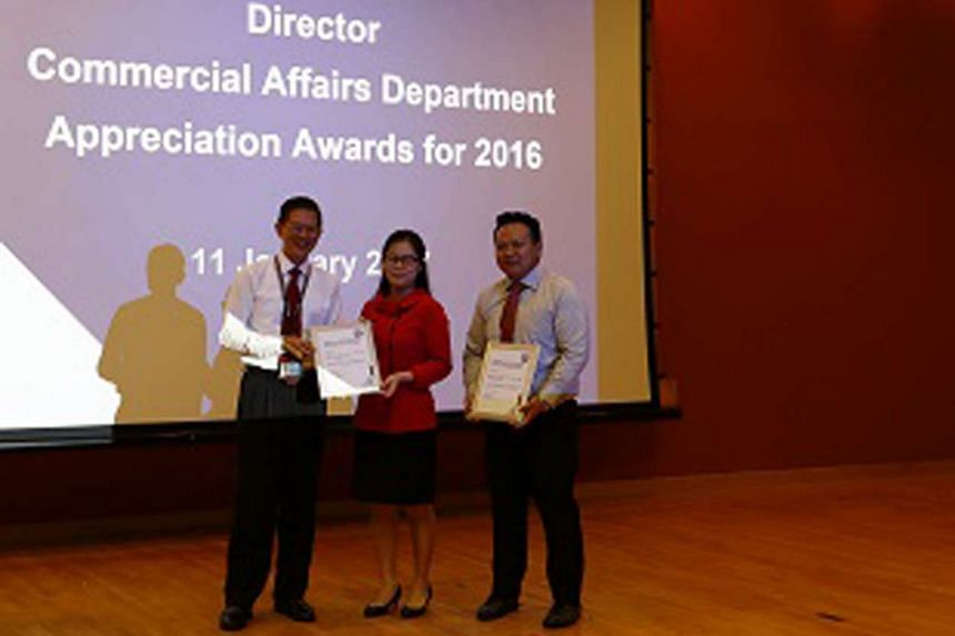 Mr Kelvin Low and Ms Alyssa Low of DBS Bank receiving the award from the Director of the Commercial Affairs Department, Mr David Chew.