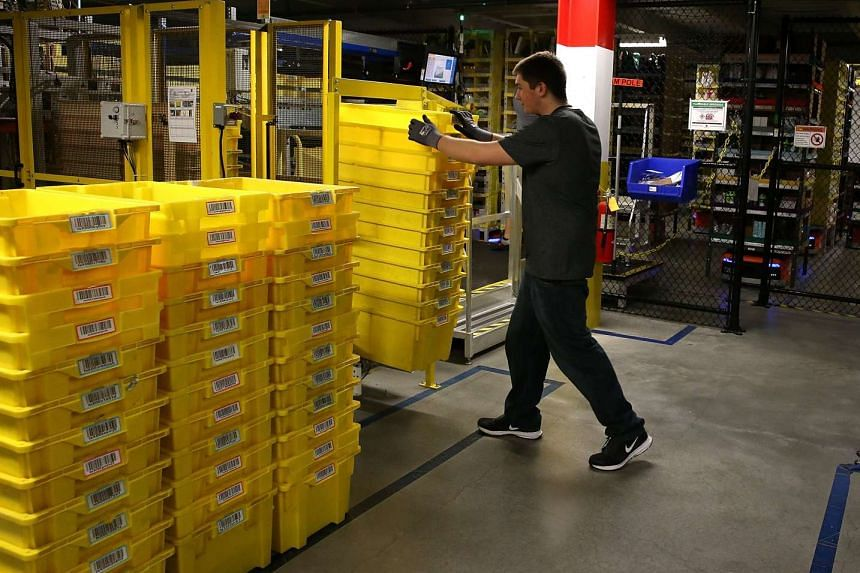 This file photo taken on Jan 19, 2015 shows an Amazon.com worker moving a stack of containers at an Amazon fulfillment center in Tracy, California.