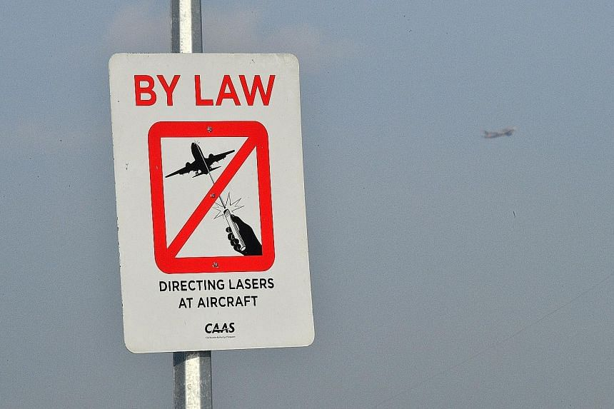 Laser lights that are shone into a plane's cockpit can confuse or distract pilots. This is especially dangerous during take-off and landing. A sign at Bedok Jetty (far right) forbids people to aim laser pointers at planes.