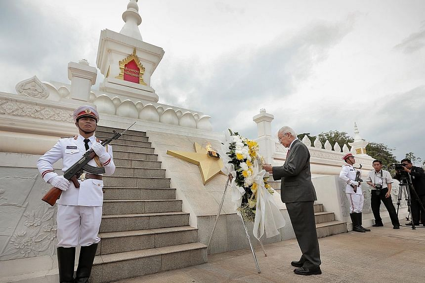 Dr Tan laying a wreath at the Unknown Soldier Monument, a memorial to Laos' war dead, yesterday.