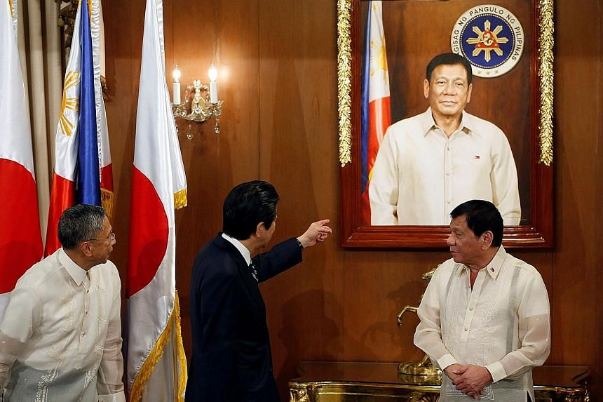 Mr Abe and Mr Duterte at the presidential palace in Manila yesterday. The Japanese Premier is keen on keeping strong ties with the Philippines as Mr Duterte shifts away from Japan's close ally, the United States.