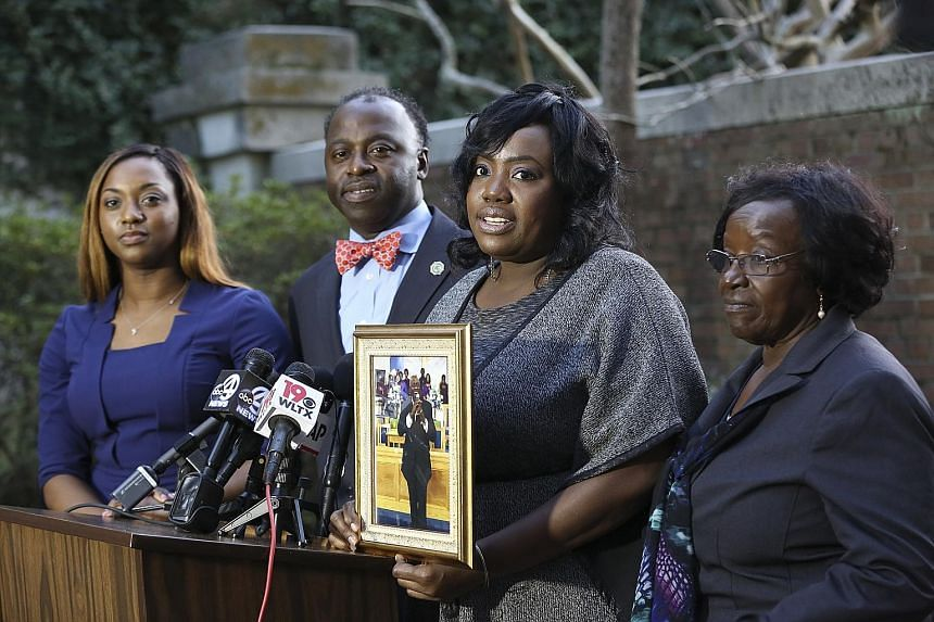Ms Rose Ann Simmons holding a portrait of her father, Reverend Daniel Simmons, who was shot dead by Roof (below). With her are (from left) Rev Simmons' granddaughter Alana, son Daniel Simmons Jr and wife Annie.