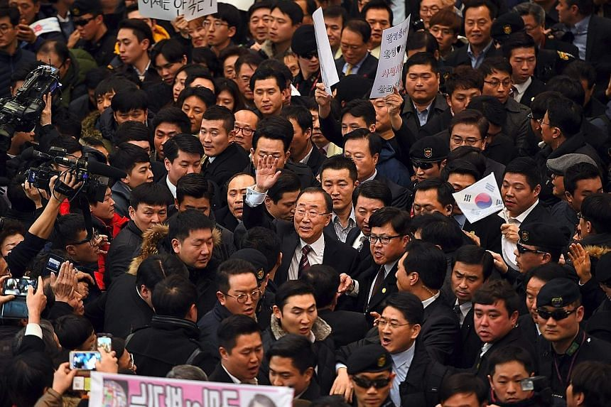 At Incheon International Airport, west of Seoul, yesterday, Mr Ban (centre, with glasses and with hand raised) was greeted by hundreds of supporters. However, his return has also drawn media scrutiny of his credentials.