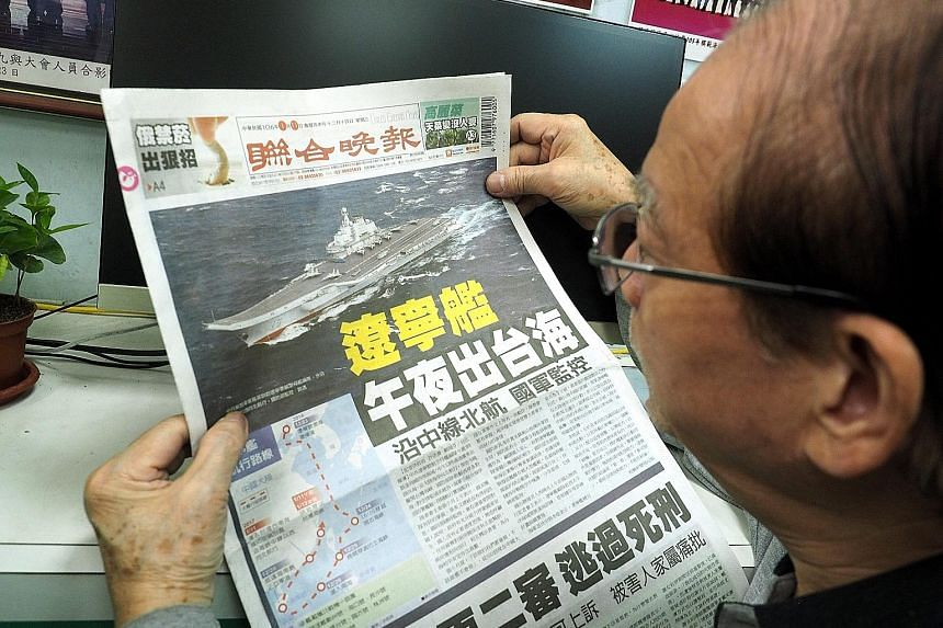A man in Taiwan reading on Wednesday about China's aircraft carrier Liaoning passing through the Taiwan Strait. China's sole aircraft carrier left the waterway separating China from the island yesterday.