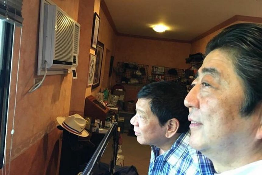 Philippines' President Rodrigo Duterte (right) and Japanese Prime Minister Shinzo Abe (centre) peering out a window at Mr Duterte's family home in Davao city.