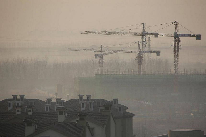 Apartment blocks are pictured next to a construction site on a hazy day in Wuqing district of Tianjin, China, on Dec 10, 2016.
